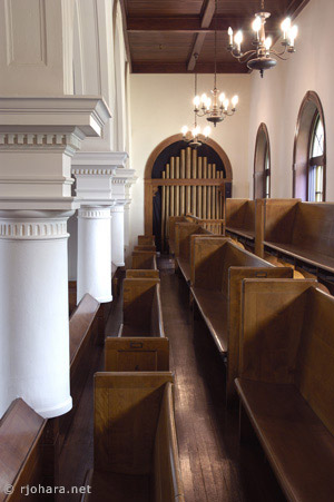 [Mead Chapel north gallery with windows, pews, and organ pipes.]